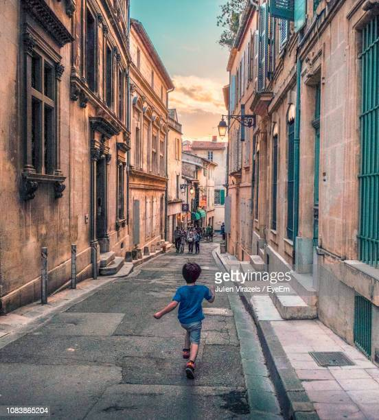 rear view of boy walking on street amidst buildings in city - bouches du rhone stock pictures, royalty-free photos & images