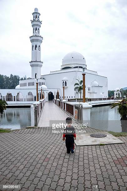 Rear View Of Boy Walking Towards Floating Mosque