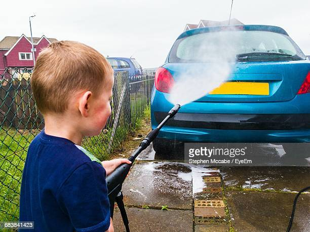 rear view of boy washing car with high pressure cleaning - high pressure cleaning stock pictures, royalty-free photos & images
