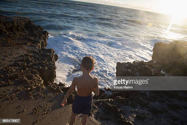 rear view of boy watching ocean waves, blowing rocks preserve, jupiter island, florida, usa - jupiter island stock photos and pictures