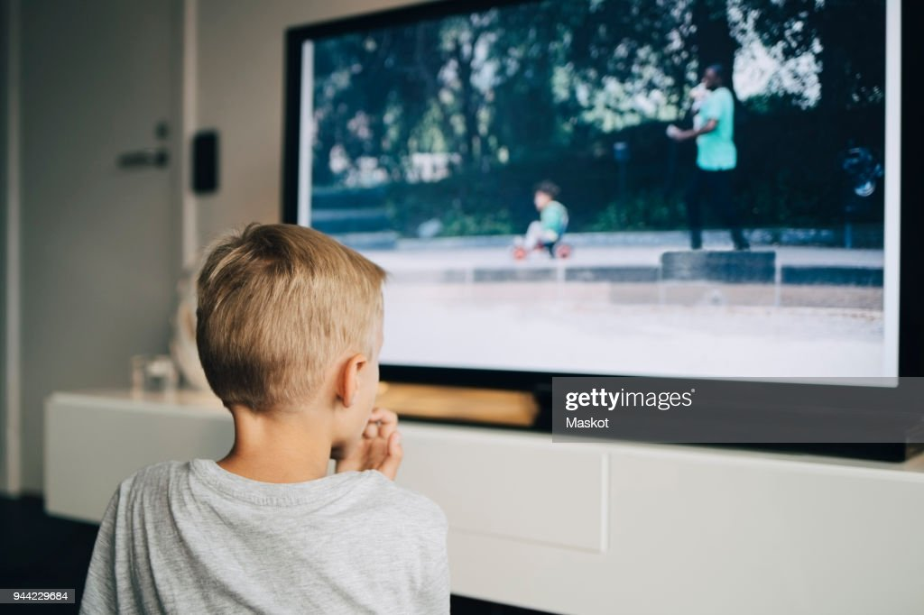 Rear view of boy watching smart TV in living room at home : Photo