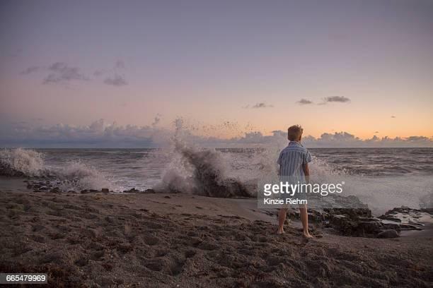 rear view of boy watching splashing waves at sunrise, blowing rocks preserve, jupiter island, florida, usa - jupiter island stock photos and pictures