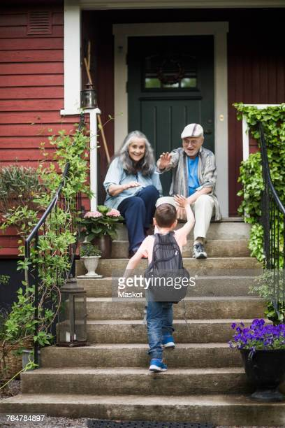 rear view of boy waving at grandparents sitting on front stoop - generation gap stock photos and pictures