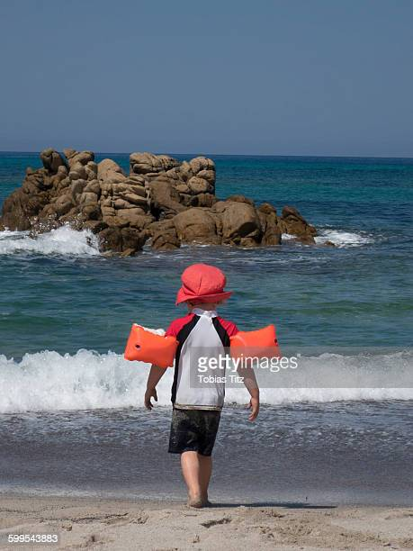 Rear view of boy wearing inflatable arm bands while walking towards sea