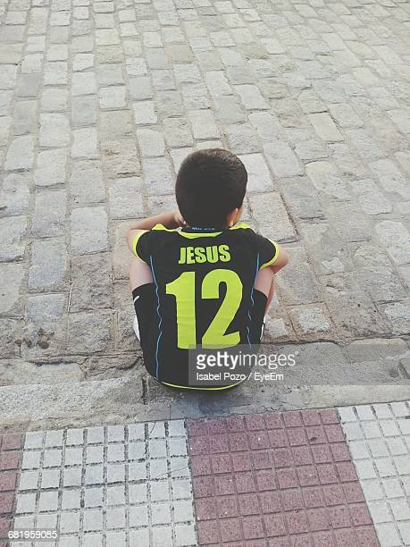 Rear View Of Boy Wearing Soccer Uniform With Text And Number 12 On Sidewalk