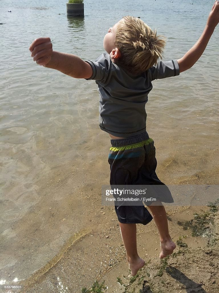 Rear View Of Boy With Arms Raised, Jumping On Beach : Foto stock
