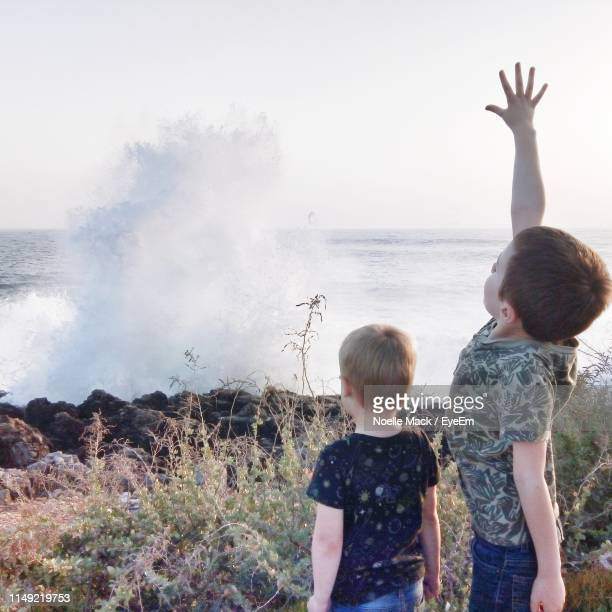 rear view of boy with arms raised standing by brother near sea - mack stock pictures, royalty-free photos & images