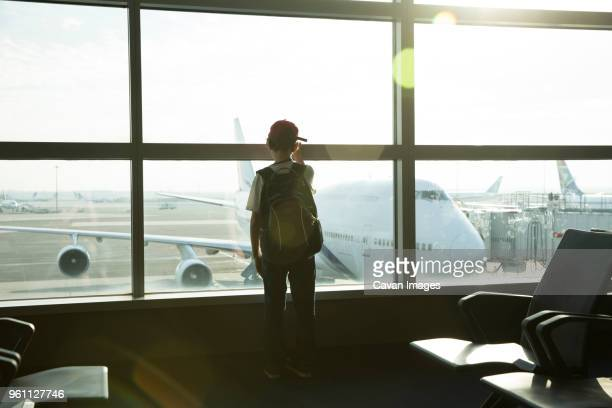 rear view of boy with backpack looking through window while standing in airport - kid in airport stock pictures, royalty-free photos & images