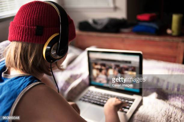 Rear view of boy with headphones using laptop on bed at home