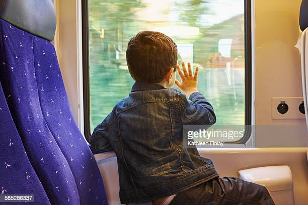 rear view of boy with his hand against train carriage window - 列車の車両 ストックフォトと画像