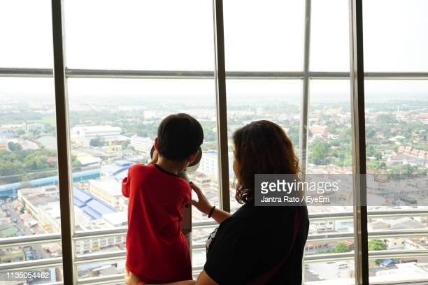 Rear View Of Boy With Mother Looking At Cityscape Through Binocular
