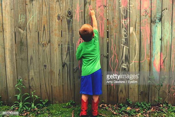 Rear View Of Boy Writing On Wooden Fence