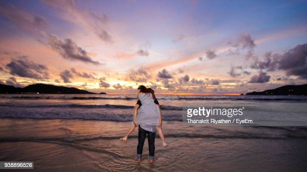 Rear View Of Boyfriend Piggybacking Girlfriend At Beach Against Sky During Sunset