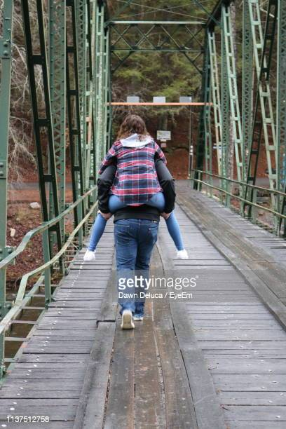 rear view of boyfriend piggybacking girlfriend while walking on footbridge - pigeon forge stock pictures, royalty-free photos & images