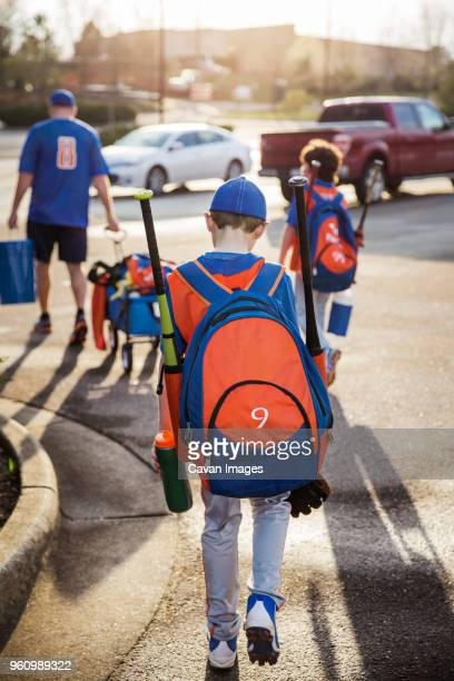 rear view of boys and baseball coach walking on street - baseball uniform stock pictures, royalty-free photos & images