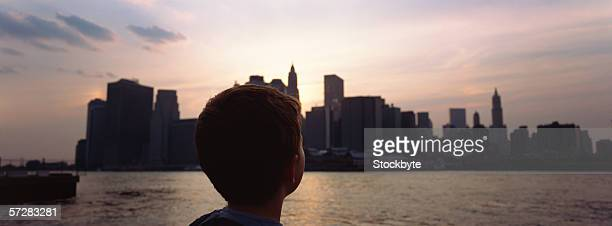 Rear view of boy's head looking at Manhattan at dusk