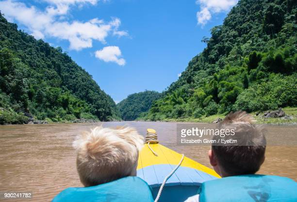Rear View Of Boys In Boat On Lake By Mountains Against Sky