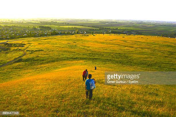 rear view of boys on grassy landscape against sky - kyrgyzstan stock photos and pictures