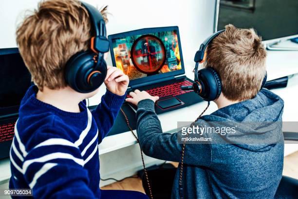 Achteraanzicht van jongens spelen van videogames op gaming laptops