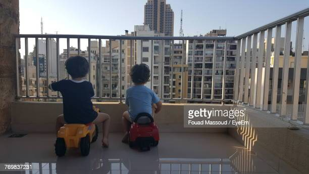 Rear View Of Boys Sitting On Toy Vehicle At Balcony In City
