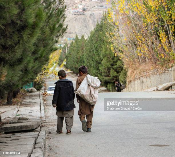 rear view of boys walking on road - afghanistan photos et images de collection