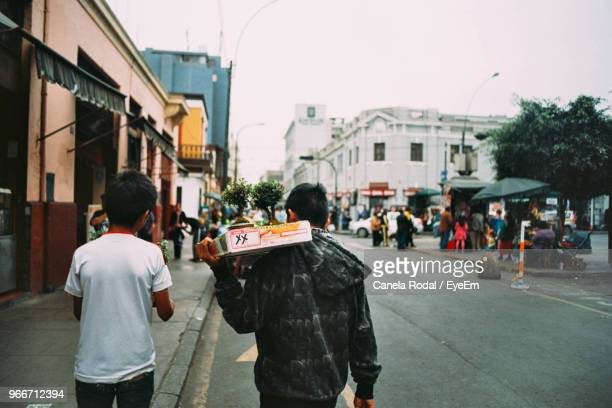 rear view of boys walking on street in city - lima stock pictures, royalty-free photos & images