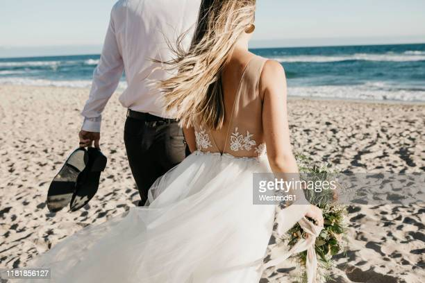rear view of bride and groom walking on the beach - marryornot stock pictures, royalty-free photos & images
