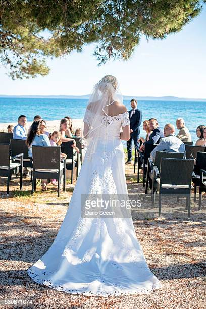 Rear view of bride at wedding ceremony on beach