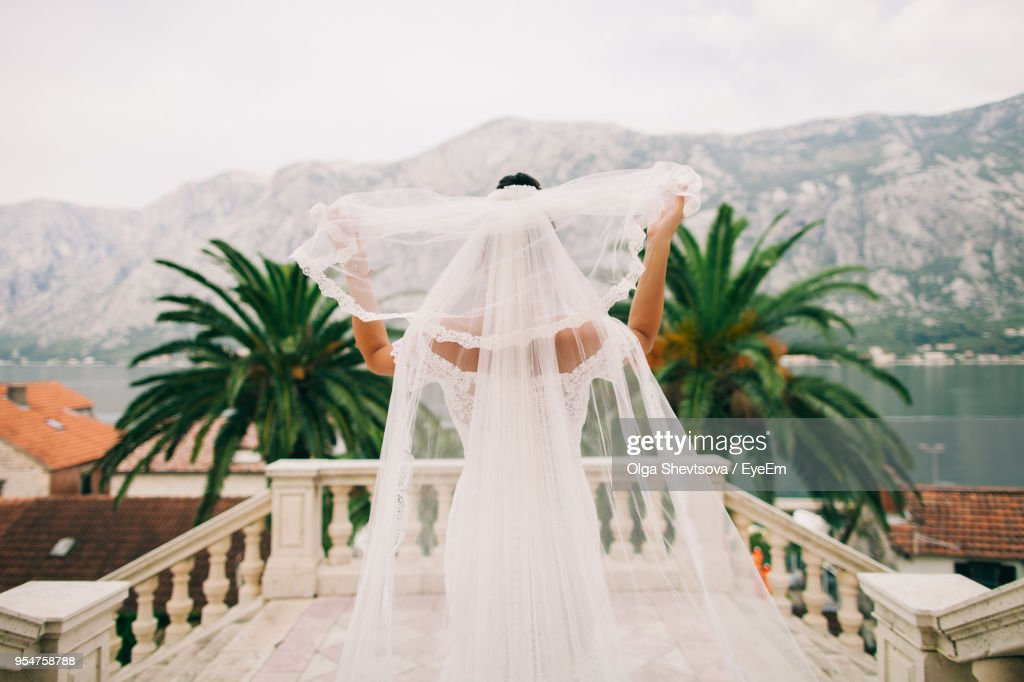 Rear View Of Bride Holding Veil At Balcony : Stock Photo