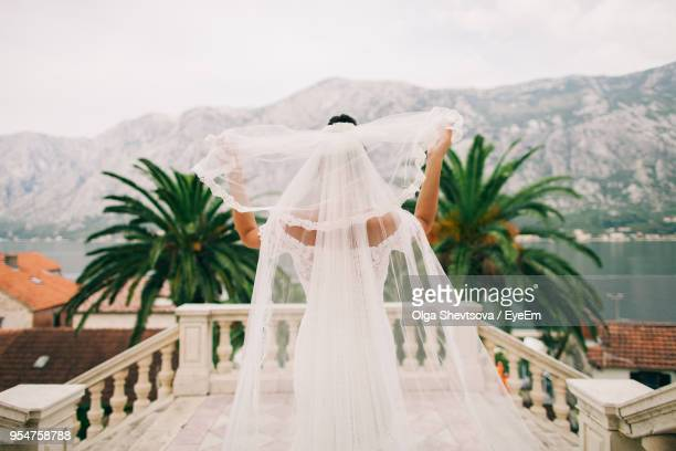 rear view of bride holding veil at balcony - wedding veil stock photos and pictures