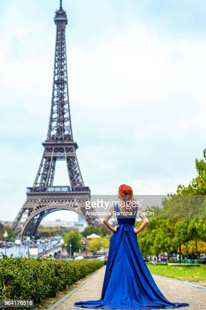 rear view of bride in blue dress standing on footpath against eiffel tower - metallic dress stock pictures, royalty-free photos & images