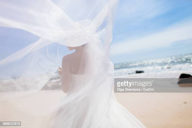 rear view of bride in dress standing at beach - ベール ストックフォトと画像