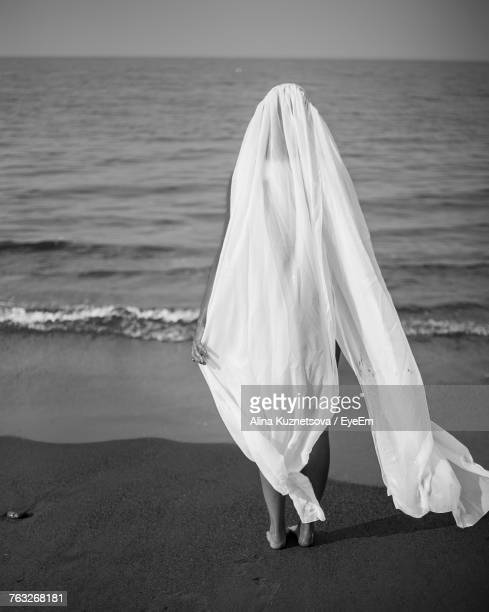 rear view of bride standing at beach - alina stock pictures, royalty-free photos & images