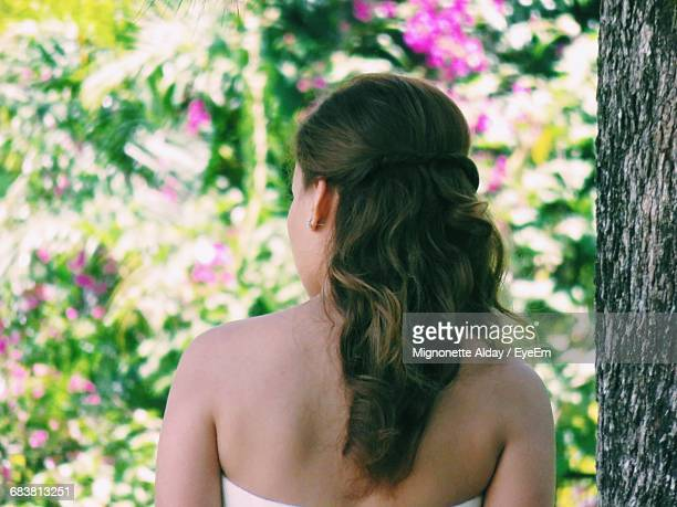 Rear View Of Bride Standing By Tree Trunk