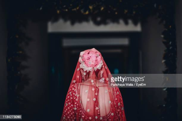 rear view of bride wearing flowers while standing at doorway - indian wedding stock pictures, royalty-free photos & images