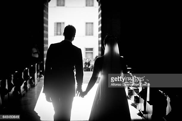 Rear View Of Bridegroom Holding Hands While Walking In Church