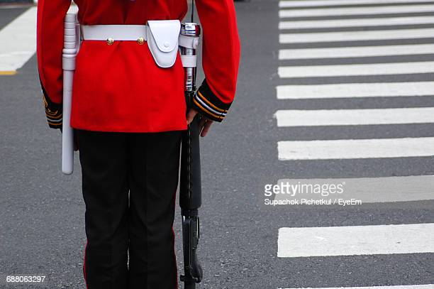 rear view of british royal guards standing by zebra crossing on road - guardsman stock pictures, royalty-free photos & images
