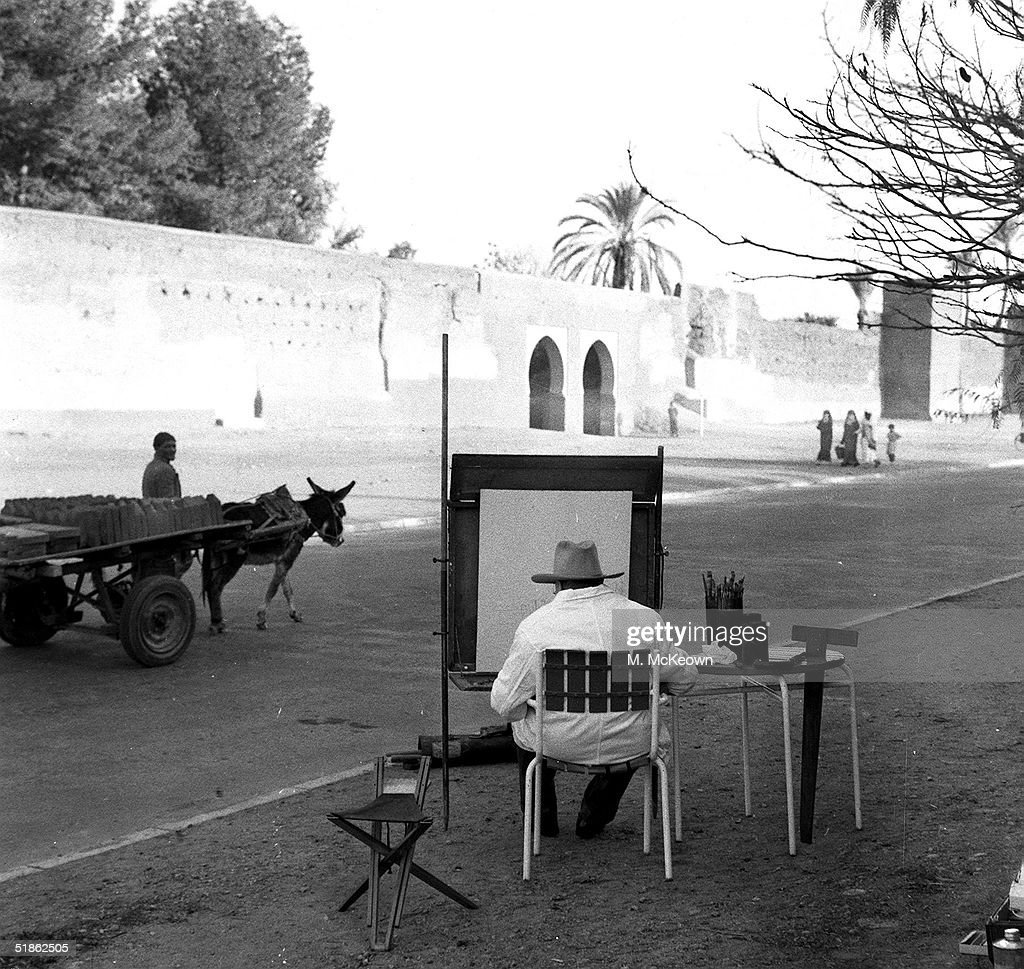 A rear view of British statesman Sir Winston Churchill painting a view of the Rue de Ramparts in Marakesh, Morocco whilst on holiday, 3rd February 1959.