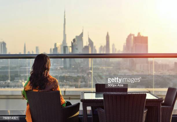 """rear view of brunette woman sitting on terrace, looking at modern skyscrapers, dubai, united arab emirates"" - image stock pictures, royalty-free photos & images"