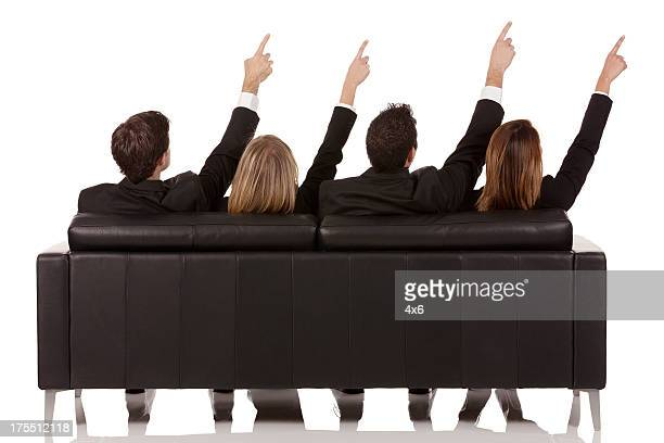 Rear view of business executives pointing upward with fingers
