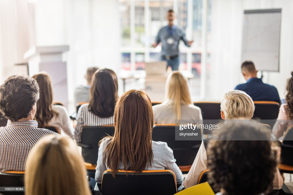 Rear view of business people attending a seminar in board room. : Stock Photo