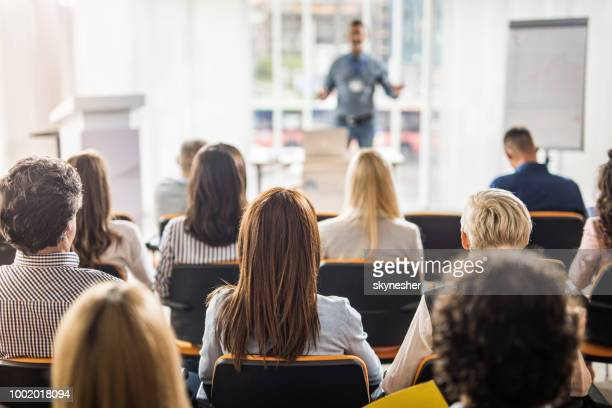 Rear view of business people attending a seminar in board room.