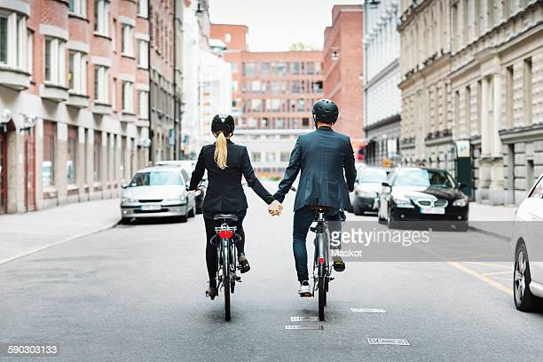 rear view of business people holding hands while riding bicycles on street - holding hands in car stockfoto's en -beelden