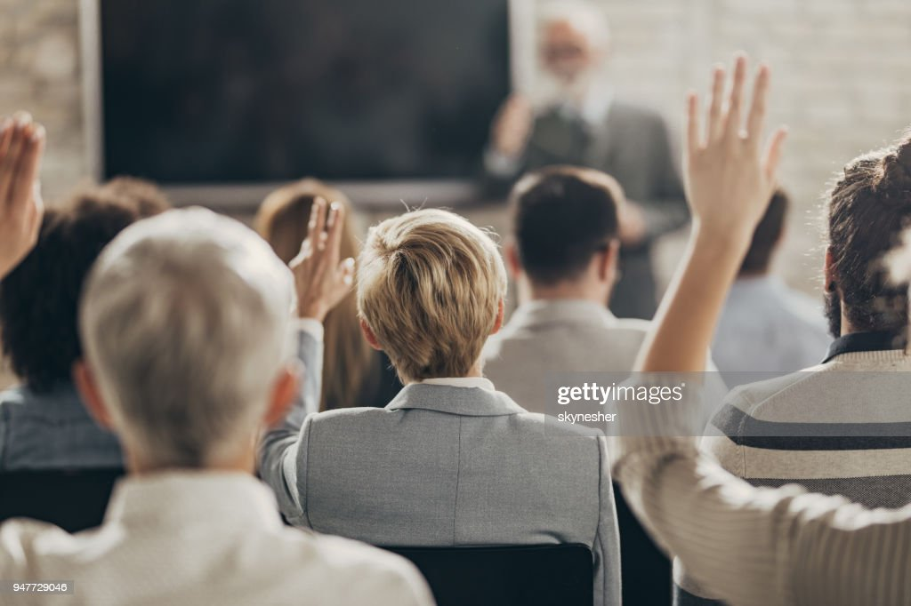 Rear view of business people raising their arms on a seminar in board room. : Stock Photo