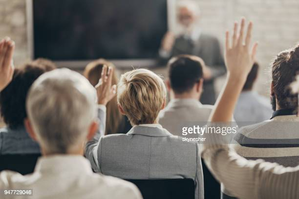 rear view of business people raising their arms on a seminar in board room. - q&a stock pictures, royalty-free photos & images