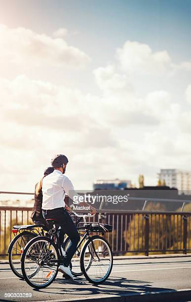Rear view of business people riding bicycles on bridge against sky