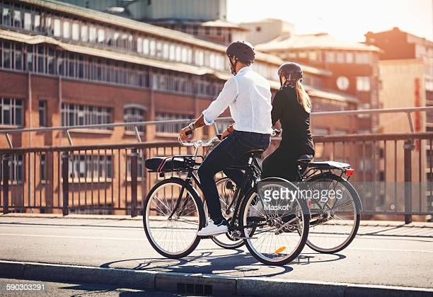 Rear view of business people riding bicycles on bridge
