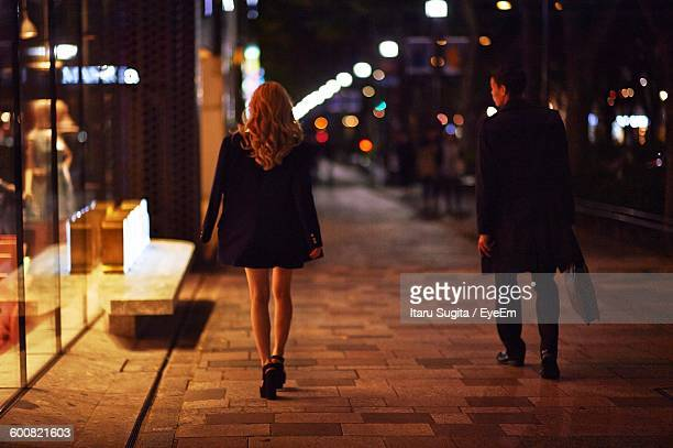 Rear View Of Business People Walking On Sidewalk At Night