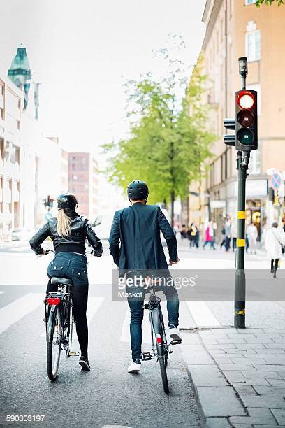 Rear view of business people with bicycles waiting at zebra crossing on city street