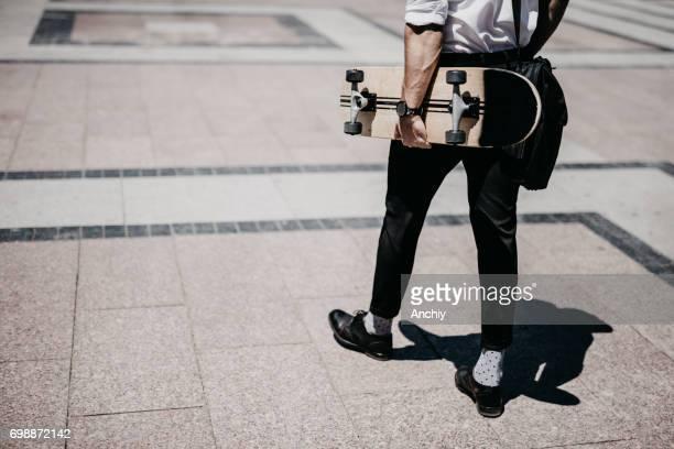 Rückansicht der Unternehmerpersönlichkeit mit skateboard
